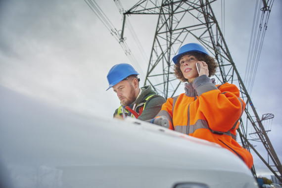 electricity engineers beneath a pylon Electricity Pylon Working Industry Occupation
